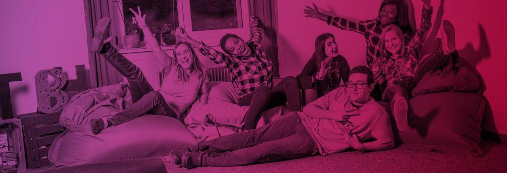 Headerbild Über Uns Junge Erwachsene sitzen auf einem Sofa und winken in die Kamera