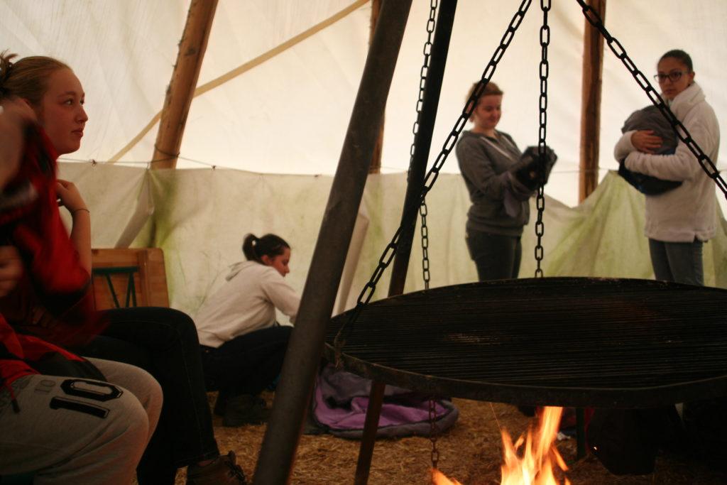 Jugendliche der La Capriola Stiftung am Lagerfeuer im Zelt