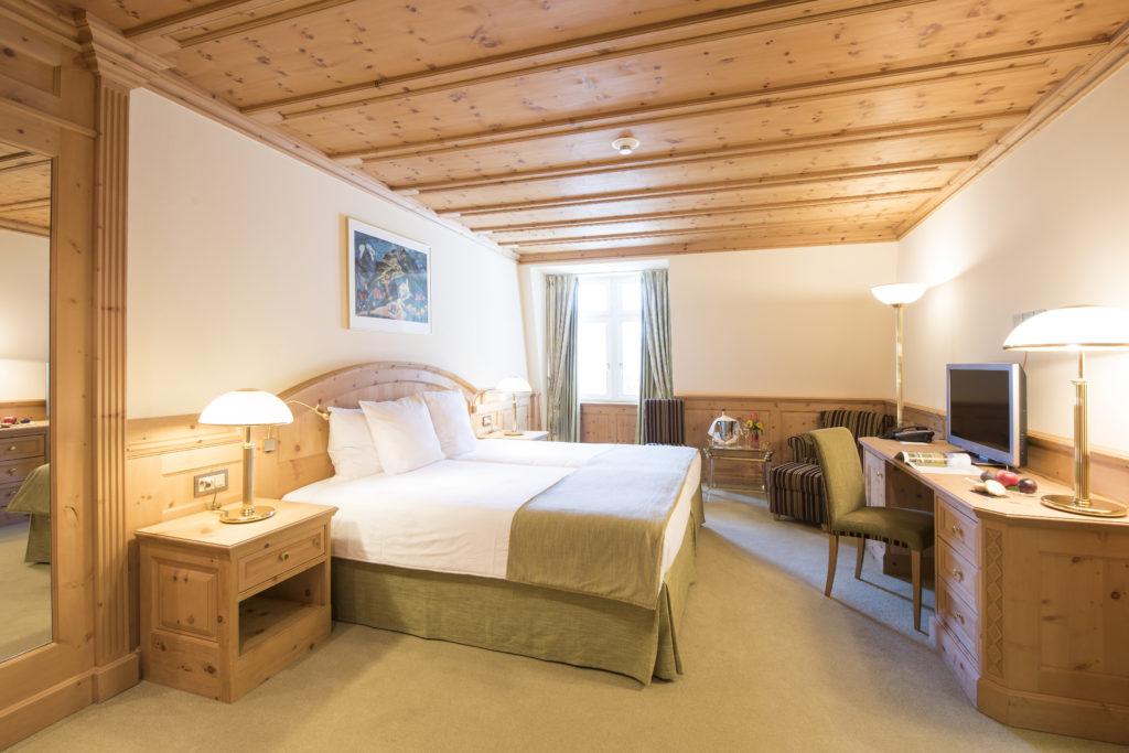 Hotelzimmer mit Doppelbett und schöner Holzdecke