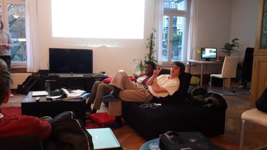 Winterblockwoche: Zwei Jugendliche auf einem Sofa winken in die Kamera