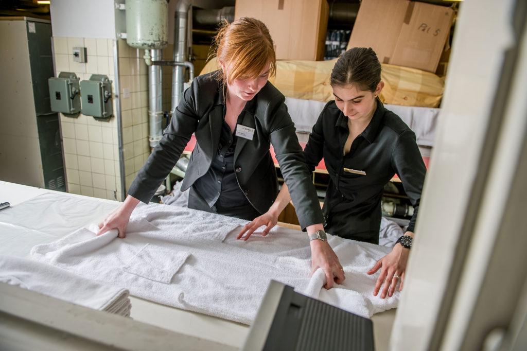 Lernende Hotelfachangestellte beim Falten von Tüchern